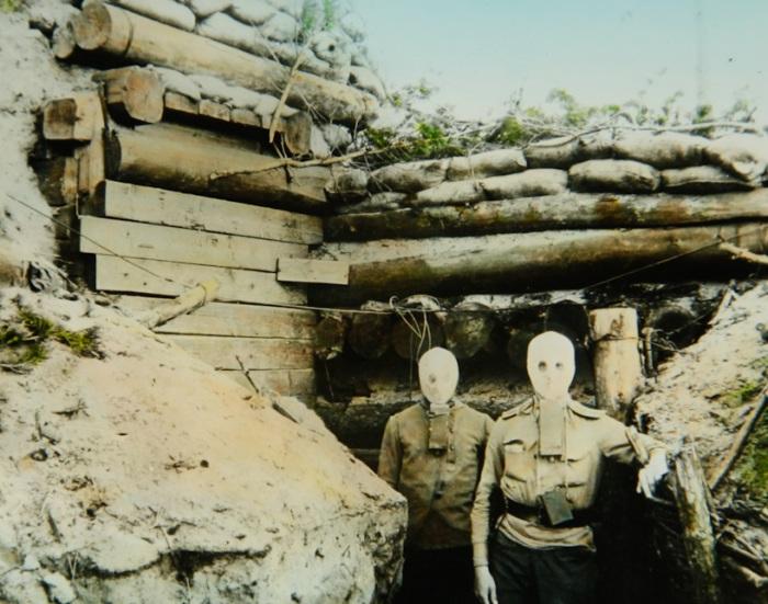 Солдаты в противогазах на передовой линии фронта.