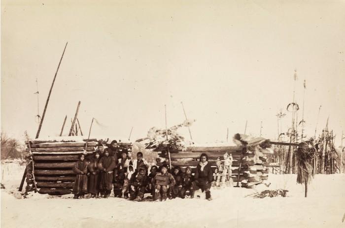 Группа айнов возле вырезанный утром инау, являющееся сакральной жертвой богам.