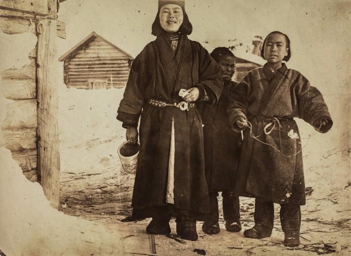 Женщина со своими детьми возле дома.