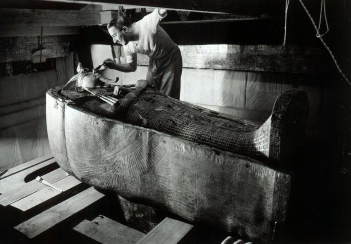 Археолог Говард Картер изучающий саркофаг с мумией фараона Тутанхамона.