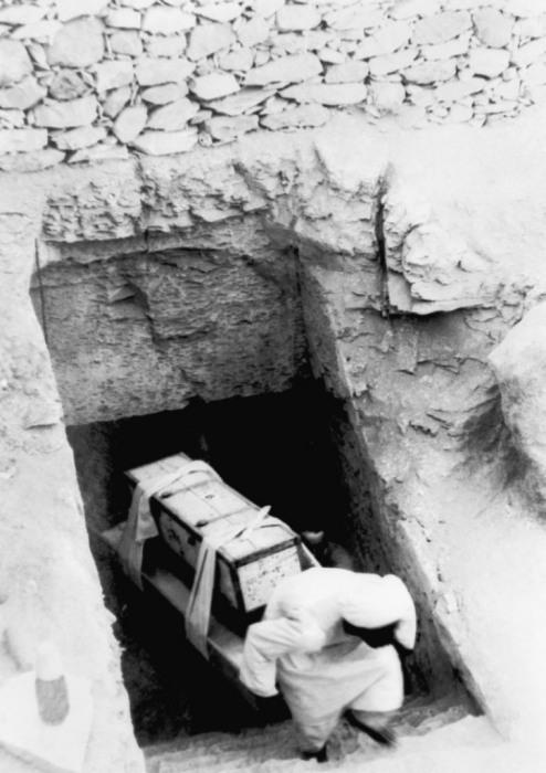 Вынос рабочими древних артефактов и сокровищ из гробницы фараона во время раскопок в Каире.