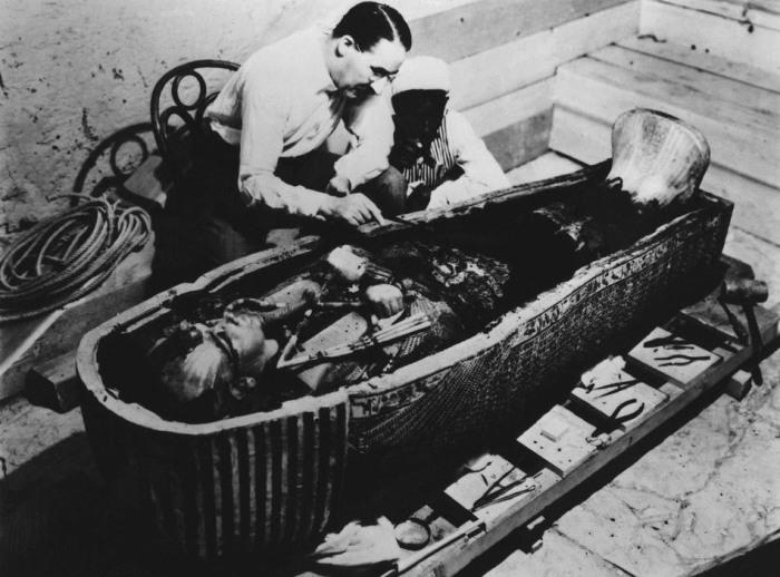 Археолог Говард Картер исследует саркофаг, найденный в гробнице Тутанхамона.