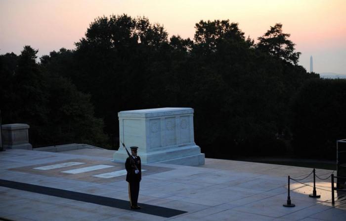 Член элитного пехотного отряда, марширующий на закате у Могилы неизвестного солдата, на Национальном Арлингтонском кладбище.