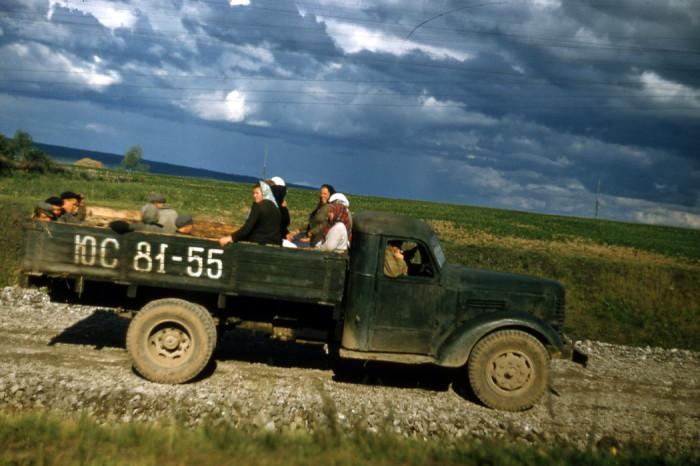 Грузовой автомобиль везёт крестьян на полевые работы.
