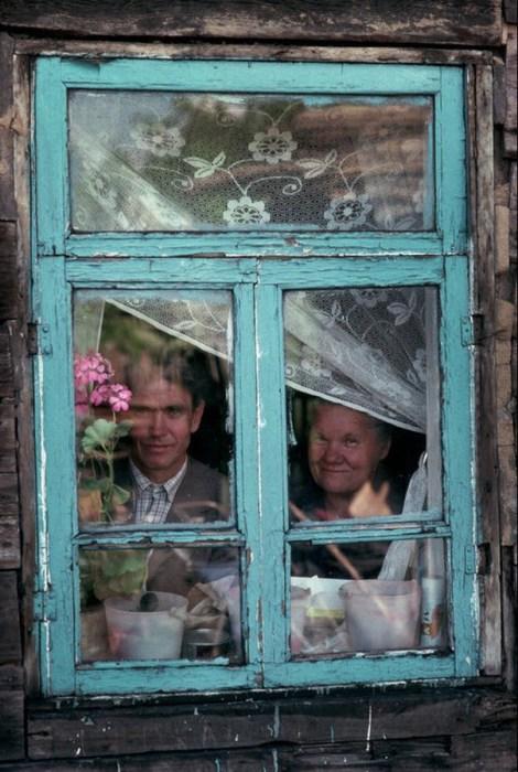 Молодой человек со своей мамой смотрящие в окно. СССР, Сибирь, 1991 год.