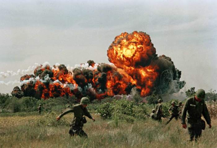 Огненные шары от взрывов напалма поблизости от расположения солдат американских войск.
