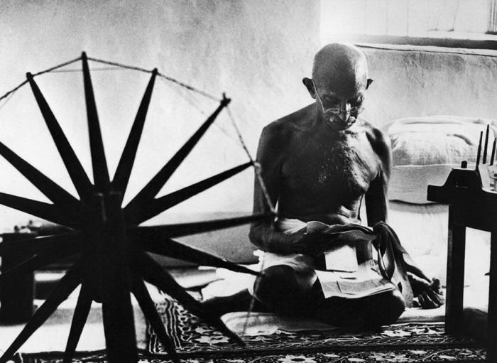 Махатма Ганди рядом с его прялкой - символом ненасильственного движения за независимость Индии от Великобритании.