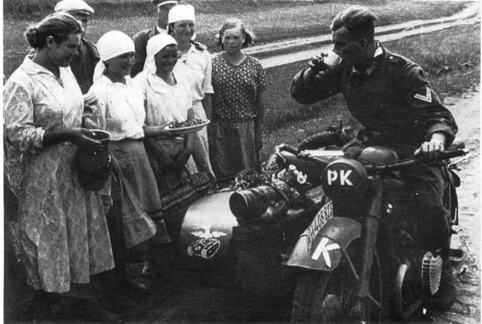 Местные жители угощают немецкого солдата едой и молоком. СССР, Украина, 1941 год.