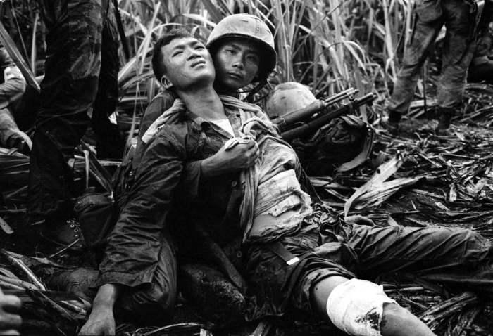 Южновьетнамский морпех успокаивает своего товарища, который был тяжело ранен северовьетнамскими партизанами в 12 км от Сайгона, 5 августа 1963 года.