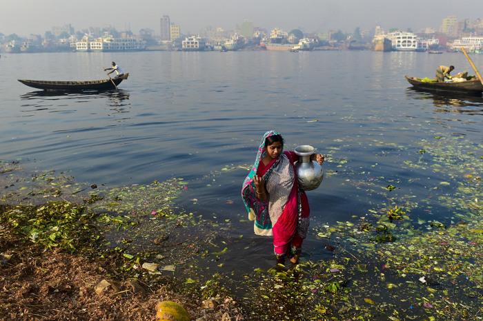 Женщина набирает воду для мытья овощей из загрязнённой реки Буриганга.