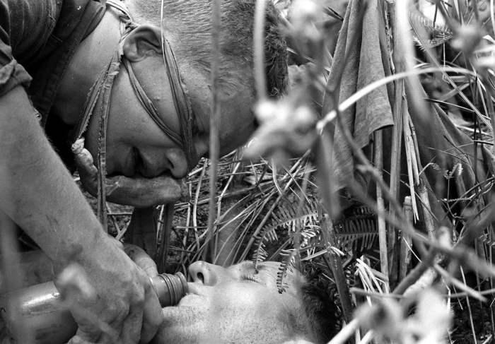 Легкораненый американский морпех поит водой своего тяжело раненого товарища во время спецоперации вдоль демилитаризованной зоны между Севером и Югом Вьетнама, 21 июля 1966 года.