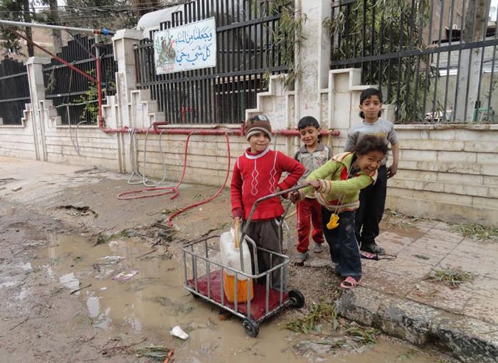 Дети набирают грязную воду в канистру в лагере палестинских беженцев.
