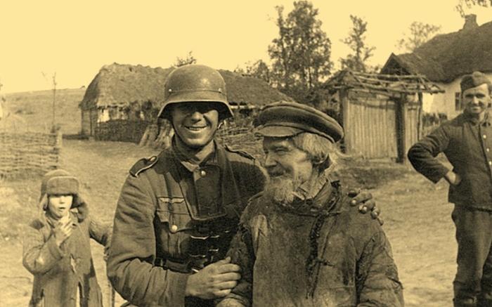 Немецкий солдат с местным жителем в оккупированной деревне. СССР, Украина, 1942 год.