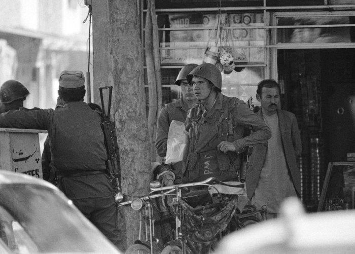 Советские солдаты выходят из афганского магазина в центре Кабула, 24 апреля 1988 года.