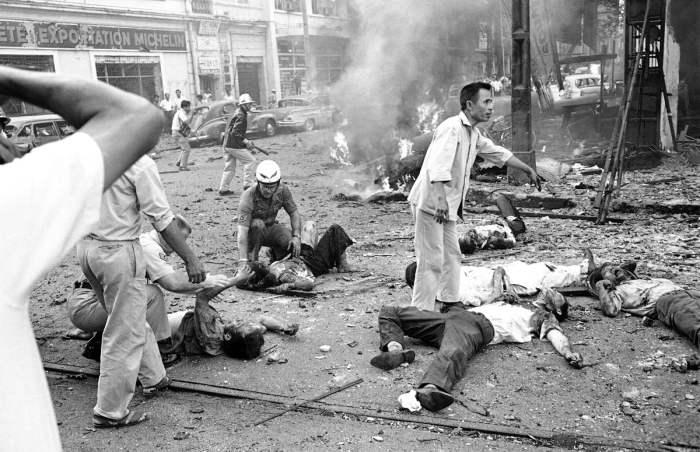 Раненые лежат на улице после взрыва бомбы у здания посольства США в Сайгоне, 30 марта 1965 года.