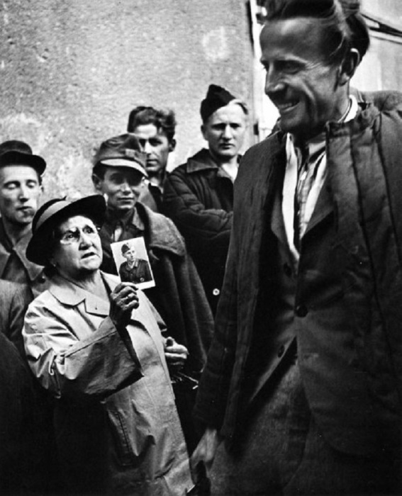 Женщина показывает фотографию своего  сына, который пропал без вести. Германия, 1947 год.