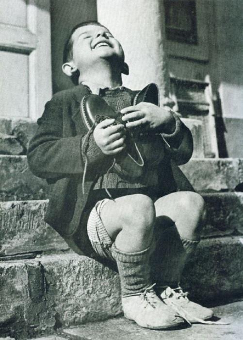 Австрийский мальчик получил новую обувь от организации Красный Крест в 1944 году.