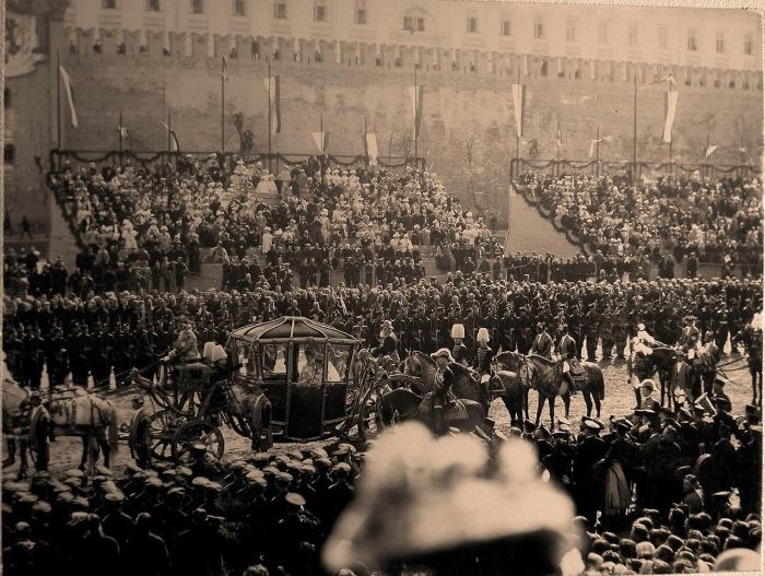 Коронационная карета императрицы Александры Федоровны проезжает мимо трибун со зрителями у Кремлевской стены на Красной площади.