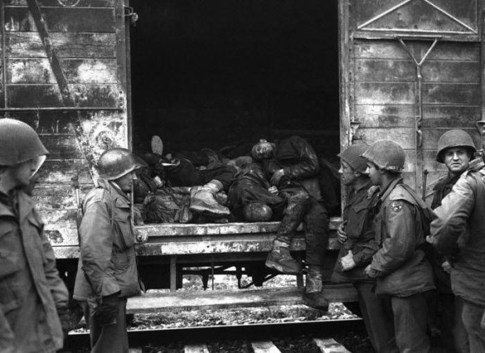 Американские солдаты осматривают железнодорожные вагоны с мертвыми телами, которые были обнаружены на железнодорожной ветке неподалёку от концентрационного лагеря Дахау в Германии.