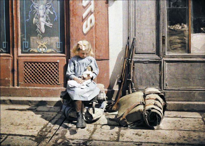 Девочка с куклой сидит на солдатском снаряжении. Франция, Реймс, 1917 год.