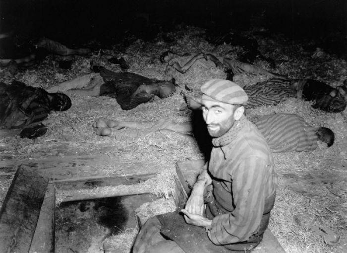 Истощенный француз сидит среди погибших в трудовом лагере Миттельбау-Дора. Германия, Нордхаузен, апрель 1945 года.