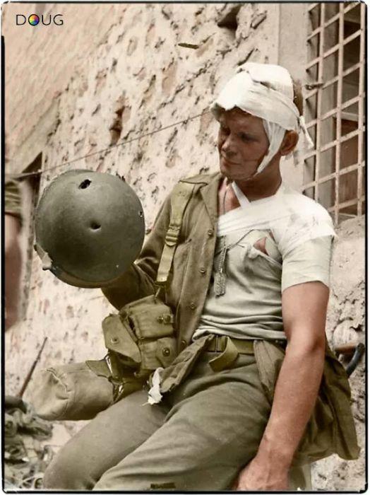 Американский солдат, пострадавший во время боёв в Италии, рассматривает каску, спасшую ему жизнь. Осень 1943 года.