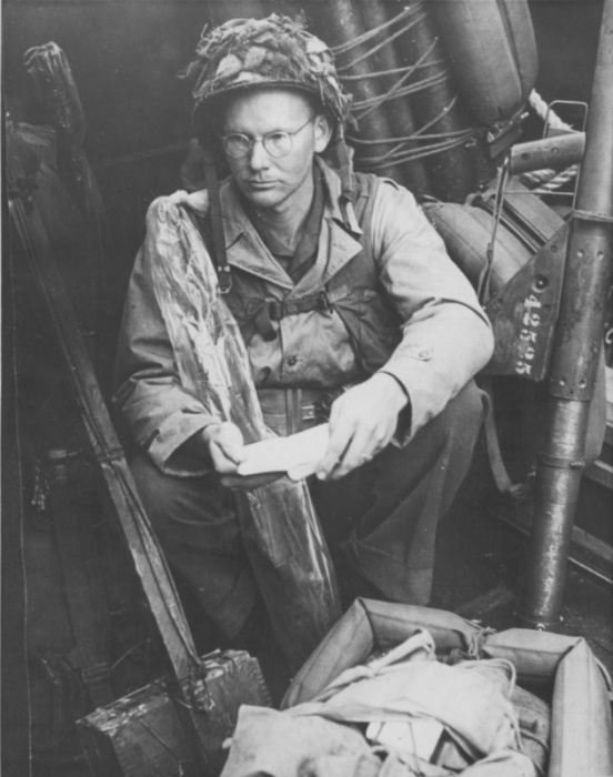 Американский пехотинец на борту десантного катера. Франция, Нормандия, 6 июня 1944 года.  На фото солдат 1–го батальона 22 пехотного полка читает Библию на борту десантного катера перед высадкой в Нормандии 6 июня 1944 года.