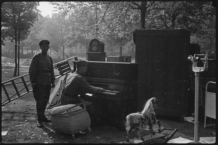 Советский солдат играет на пианино в пригороде Берлина в мае 1945 года.