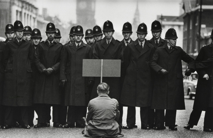 На фото выдающегося военного фотографа современности Дока МакКуллина запечатлено противостояние мужчины, сидящего в одиночном антивоенном пикете, и лондонских полицейских «бобби» на улице Уайтхолл недалеко от здания Британского парламента во время Карибского кризиса в 1962 году.