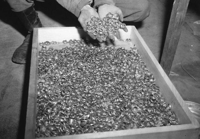 Американский солдат осматривает тысячи золотых обручальных колец, которые были изъяты у евреев немцами в Солт Хайльбронн.