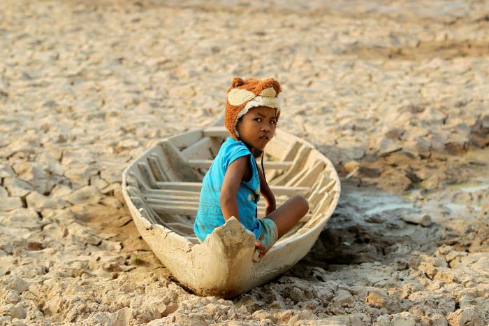 Девочка в лодке посреди высохшего пруда после засухи в провинции Кандаль.