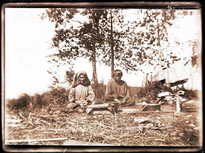 Мужчина и женщина занимающиеся привычной работой в районе реки Вах. Нижневартовский район, Ханты-Мансийского автономного округа, 1912 года.