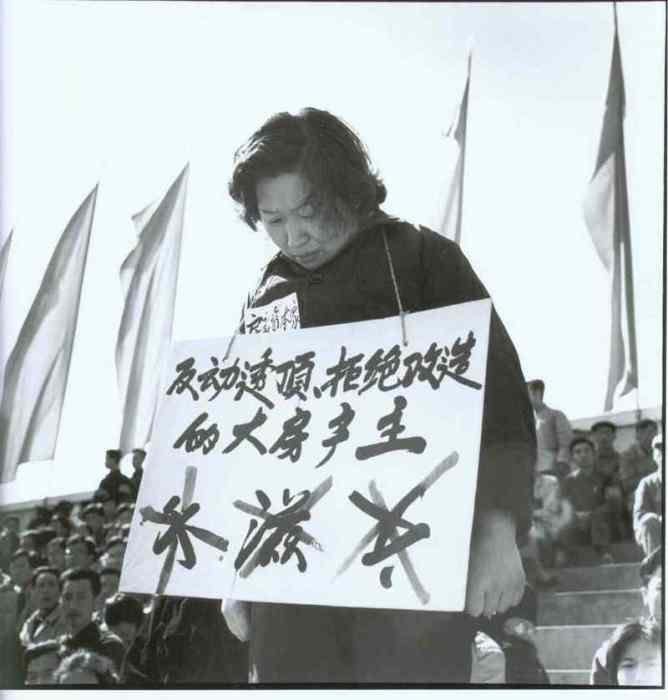 Женщина, стоящая на стуле в центре Площади Красных Охранников.