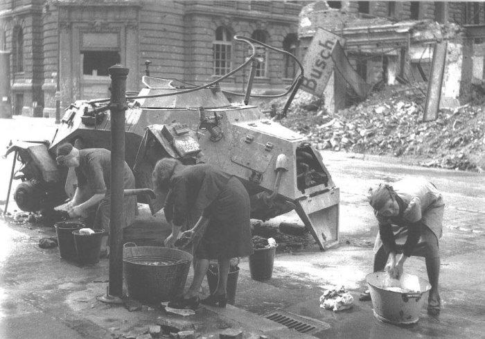 Женщины стирают белье рядом с подбитым броневиком. Германия, Берлин, 3 июня 1945 года.
