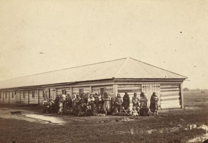 Заключённые с детьми стоят перед бараком.