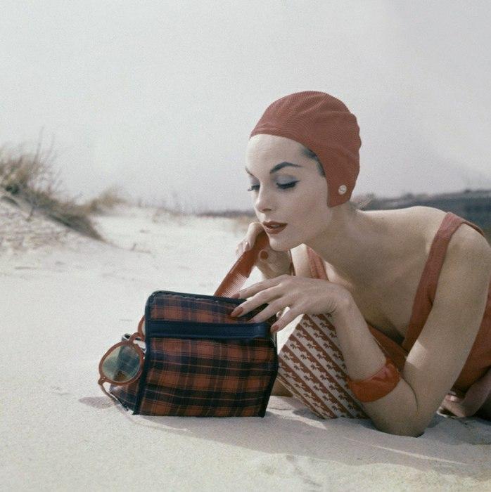 Девушка, достающая из сумки расческу на пляже. 1950-е годы.