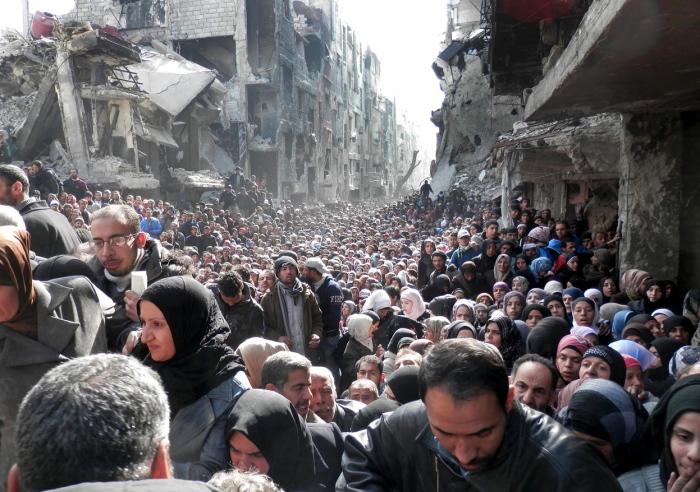 Жители осаждённого лагеря для беженцев Ярмук стоящие в очереди за водой и продовольствием. Сирия, Дамаск, 31 января 2014 года.