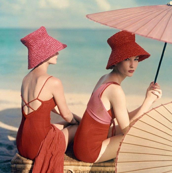 Две девушки в красных купальниках под зонтом. 1950-е годы.