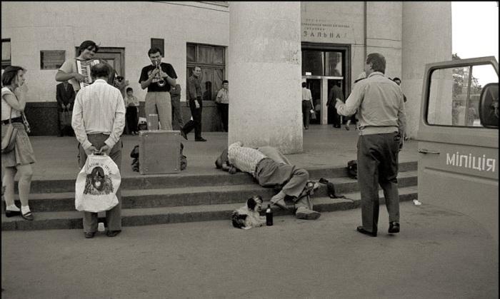 Пьяный мужчина на ступеньках Железнодорожного вокзала. СССР, Киев, 1991 год.