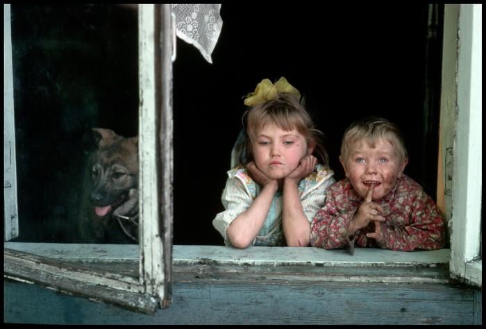 Дети, выглядывающие из окна. СССР, Новокузнецк, 1991 год.