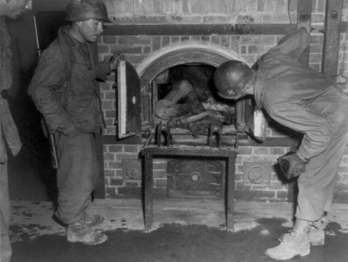 Американские солдаты осматривают мёртвые тела, находящиеся в печи крематория.