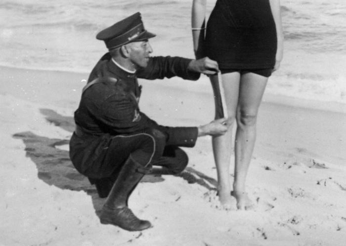 Полицейский измеряет у девушки на пляже длину купальника на соответствие его размеров установленным требованиям. США, Вест Палм Бич, 1925 год.