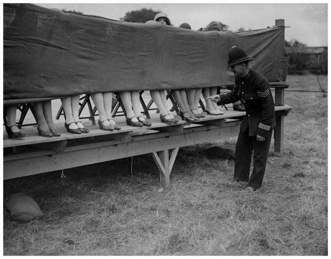 Офицер полиции выступает судьёй на конкурсе женских лодыжек в Лондоне в 1930 году.