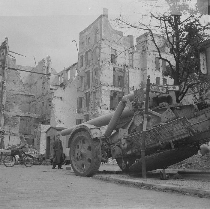 Мирный житель осматривает брошенную на улице Берлина немецкую 210-мм тяжелую полевую гаубицу 21 cm Mörser 18.