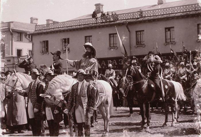Церемониймейстеры и один из герольдов объявляют горожанам о дне священного коронования на одной из улиц города.