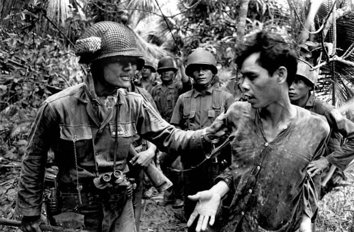 Командир батальона войск Южного Вьетнама капитан Тхач Куен угрожает применением насилия захваченному в плен северовьетнамскому солдату в дельте реки Меконг в 1965 году.