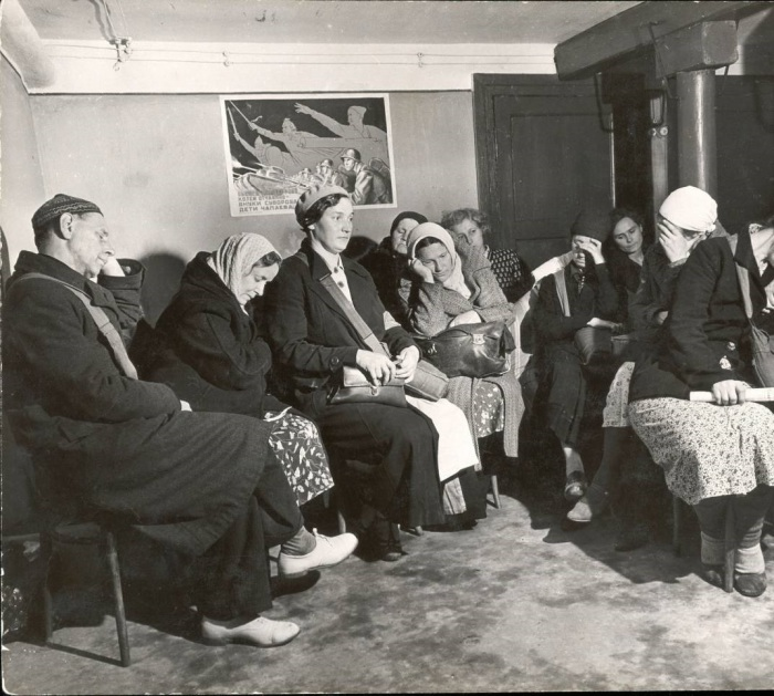 Жители дома, находящиеся во временном бомбоубежище по месту жительства и ожидающие конца бомбардировки. СССР, 1941 год.
