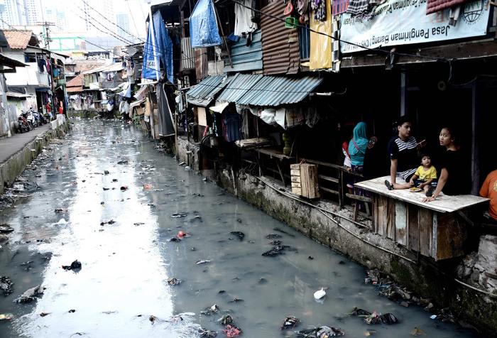 Загрязнённый канал в трущобах Джакарты.