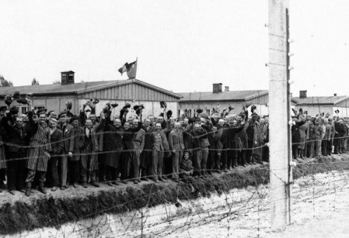 Заключенные у находящегося под током забора концентрационного лагеря Дахау приветствуют американских солдат.