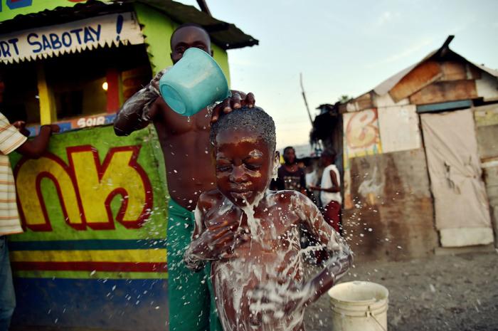 Отец купает сына на улице в Порт-о-Пренсе.